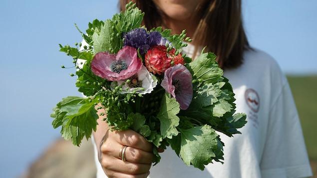 Un bouquet de fleurs tenu par Mylène Montplaisir, en arrière-plan.