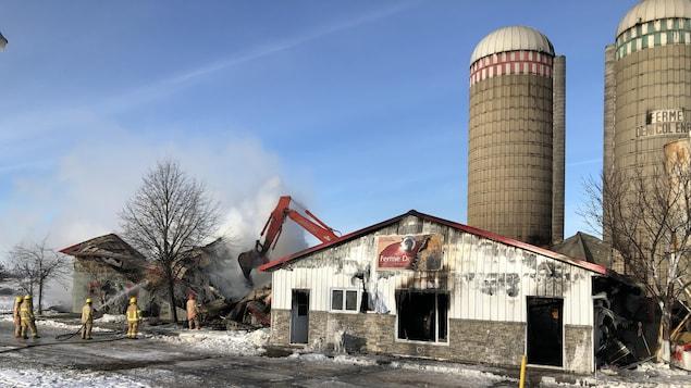 Ferme détruite avec pompiers qui arrosent encore