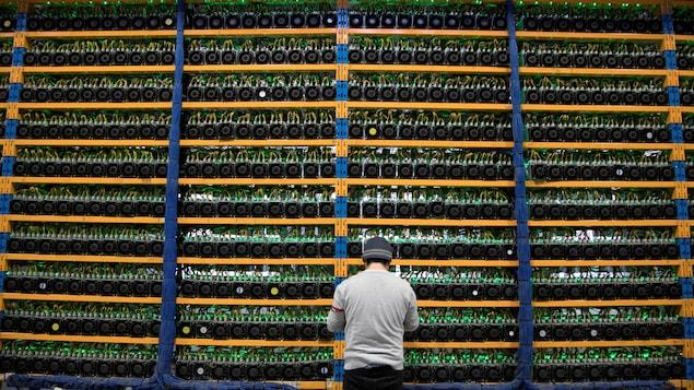 Un ouvrier vérifie les ventilateurs sur les mineurs, à l'exploitation agricole cryptocurrency, Bitfarms, à Farnham.