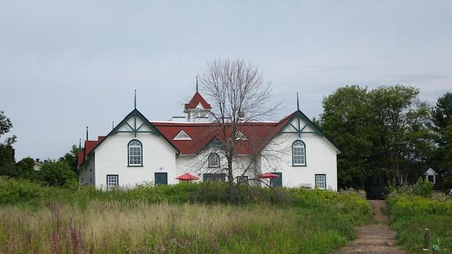 La photo montre un bâtiment de ferme blanc et un champ de fleurs