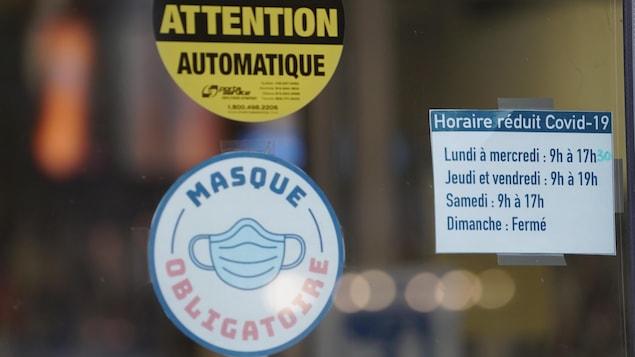 Une porte avec des affiches rappelant le port obligatoire du masque et des horaires d'ouverture réduite en raison de la COVID.