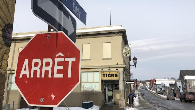 Un panneau d'arrêt avec, au-dessus, les noms des rues Frontenac et Eddy. Derrière, la façade du Tigre Géant et la rue Eddy en perspective.