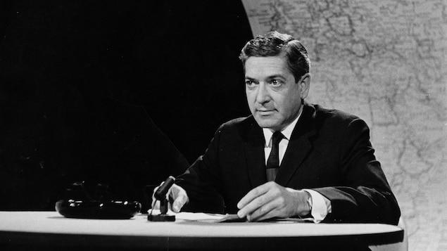 Dans un studio de télévision, Fernand Seguin est assis à un pupitre sur lequel repose un micro de table. En arrière-plan, une immense carte du monde.