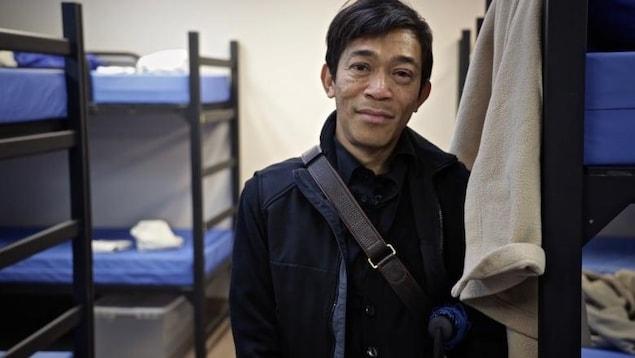 Un homme regarde devant, avec des lits superposés en arrière-plan.