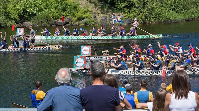 Des bateaux-dragons voguent sur une rivière.