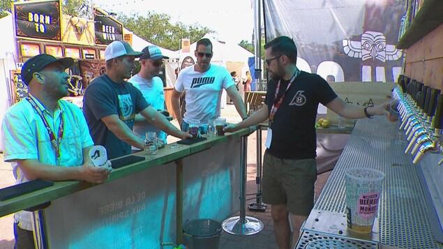 Quatre visiteurs se font servir des bières par un représentant.