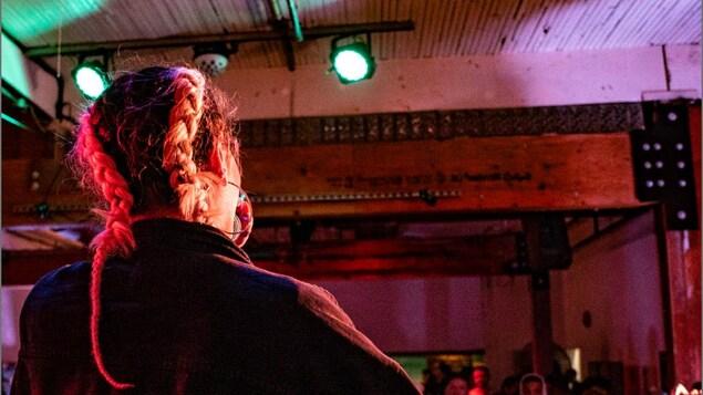 Photographie d'une chanteuse de dos sur scène devant son public.