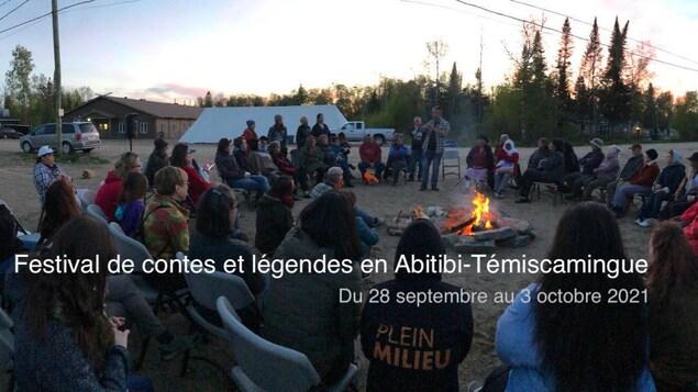 Un public assis en cercle autour d'un feu de camp à l'extérieur.