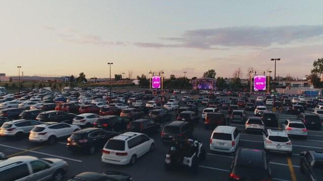 Des voitures garées devant une scène dans un stationnement.