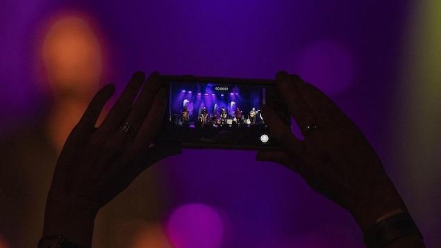 Les mains de quelqu'un qui enregistre une vidéo avec un téléphone cellulaire.