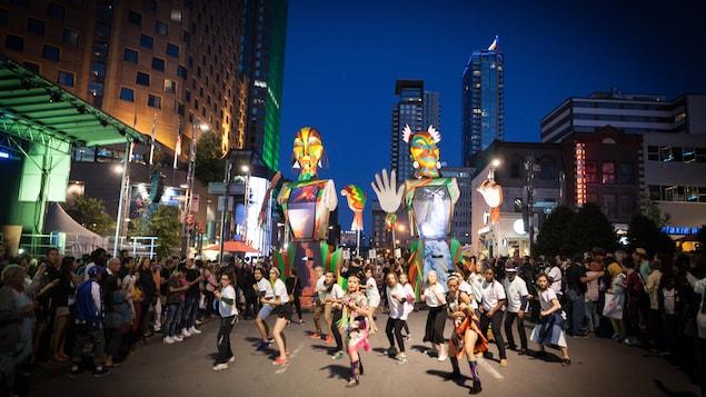 Des marionnettes géantes suivent une quinzaine de danseurs à qui la foule fait place.