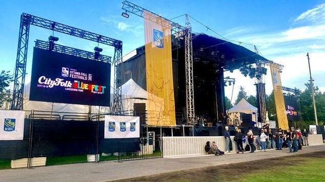 Des personnes rassemblées devant une scène, avant un spectacle extérieur.
