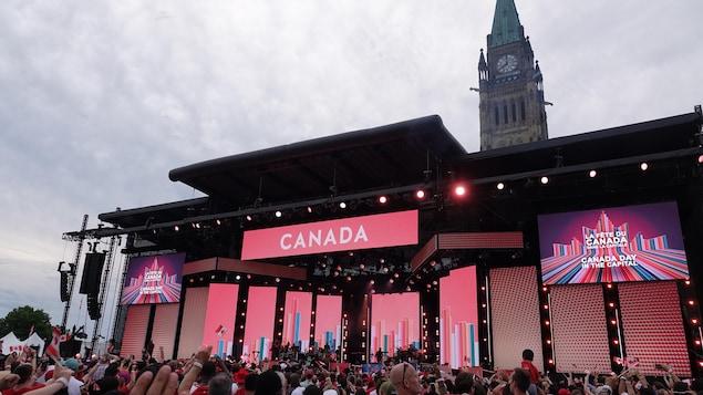 Photo prise dans la foule devant la scène pour le spectacle de la fête du Canada avec en arrière-plan la tour de la paix.