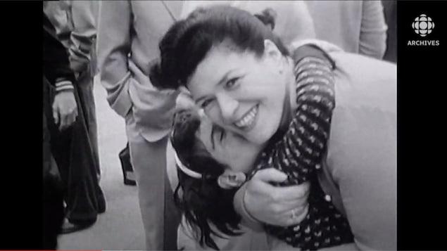 Une enfant prend sa mère par le cou en l'embrassant la joue.