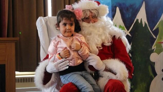 Une enfant assis sur les genoux d'un père Noël.