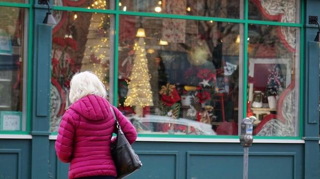 Une dame devant une vitrine décorée pour les Fêtes.