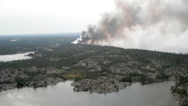 Vue aérienne d'un secteur boisé. Une épaisse fumée et des flammes peuvent être apperçus.