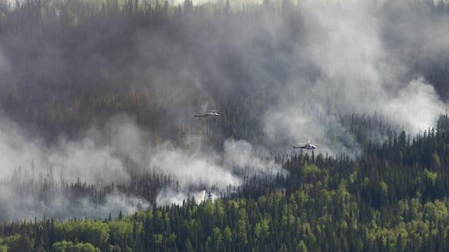 Un hélicoptère jette de l'eau sur les flammes àa l'ouest de High Level