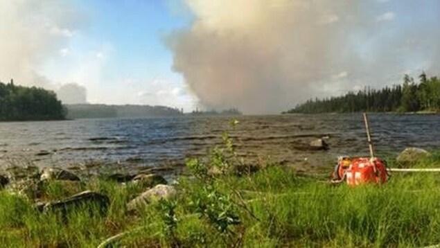 Le Nipigon District Fire Number 29, qui s'étend actuellement sur 1000 hectares, se trouve à une vingtaine de kilomètres au nord de la Première Nation de Nibinamik. Sur la photo prise au bord d'un lac, on voit de la fumée dans le ciel.
