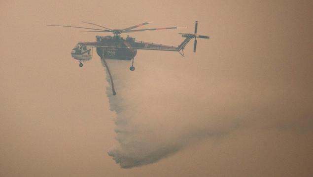 Un hélicoptère dans les airs. Il est difficile de le voir en raison de l'épaisse fumée dans le ciel.