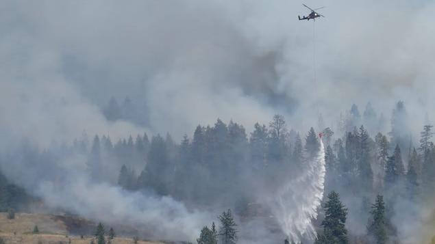 Un hélicoptère verse de l'eau sur un feu de forêt près de Vernon