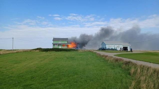 Une résidence en feu dont la fumée se dirige vers la maison voisine. Des citoyens sont rassemblés devant celle-ci.