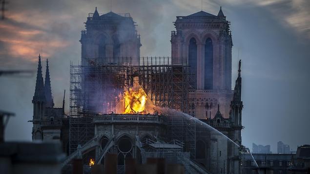 Les pompiers envoient d'immenses jets d'eau pour éteindre les flammes qui ravagent le centre de la cathédrale.