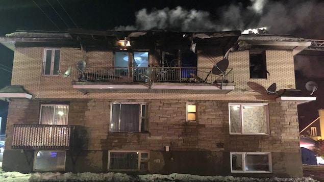 De la fumée émane du toit de l'immeuble.