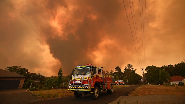 Un camion de pompier circule sur une route sous un ciel rempli de fumée.