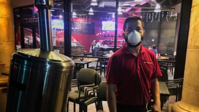 Un serveur dans un restaurant porte un masque pour se protéger des particules et de la fumée.
