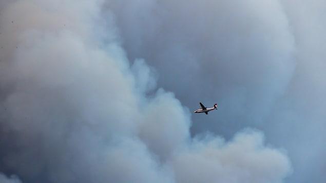 Un avion-citerne vole à proximité d'un immense nuage de fumée.