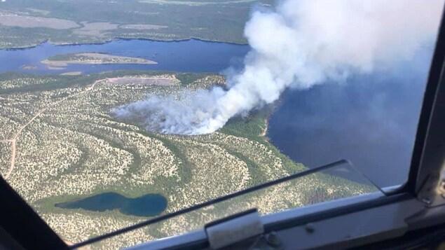 Vue aérienne d'une partie du Labrador. Des immenses colonnes de fumées émanent de la terre.