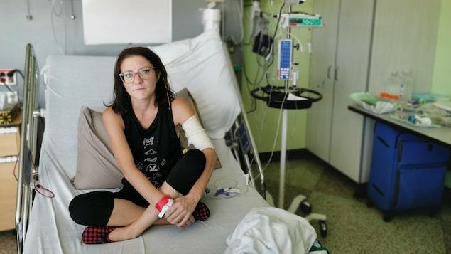 Une femme est assise sur un lit d'hôpital.