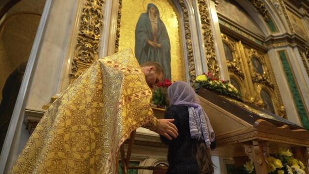 Un prêtre se penche sur une fidèle dans l'église.