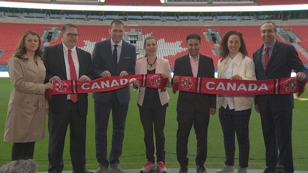 la ministre fédérale des sports Kirsty Duncan est avec des membres de l'Association canadienne du soccer et une banderole avec écrit dessus « Canada » devant le BMO Field de Toronto, ils sourient et posent pour une photo de groupe.