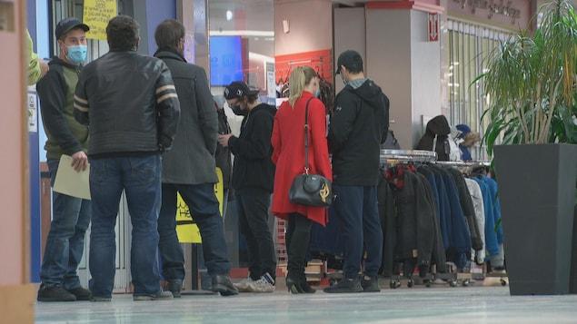 Des gens qui attendent en file avant d'entrer dans un commerce.