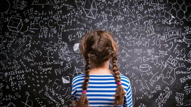 Une fille de dos qui regarde un grand tableau noir avec des formules mathématiques.