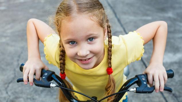 Une jeune fille fait du vélo.