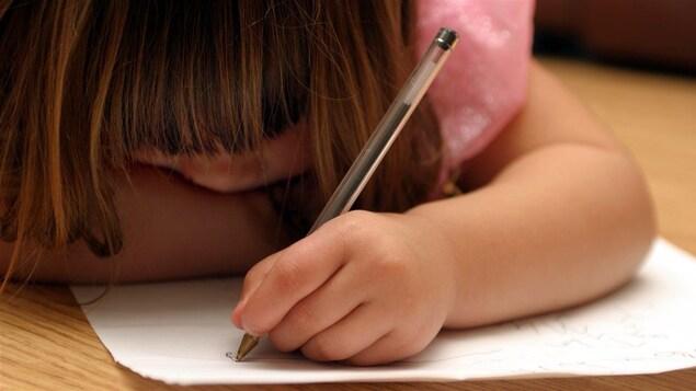 Une fillette gauchère écrit sur une feuille de papier