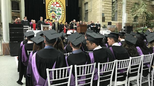 Des étudiants sont assis à leur cérémonie de remise des diplômes.