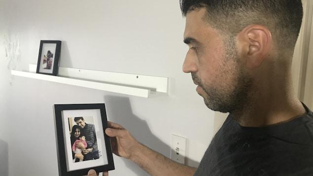 Un homme tend un cadre avec une photo