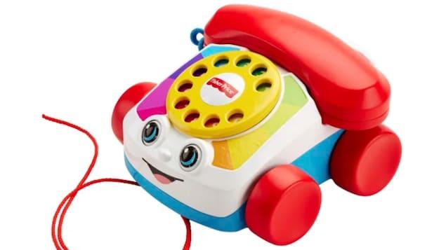 Un téléphone jouet souriant avec des yeux sur un fond blanc.