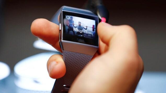 Une personne tient un bracelet connecté Fitbit dans sa main.
