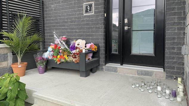 Des fleurs et des peluches ont été déposées sur un banc alors que des chandelles sont aussi sur le balcon.