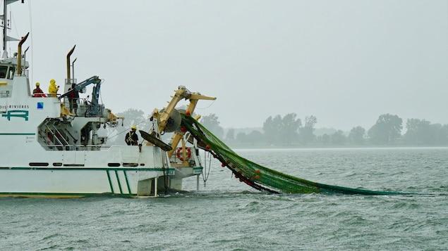 Un bateau de pêche tire un filet sous la pluie.