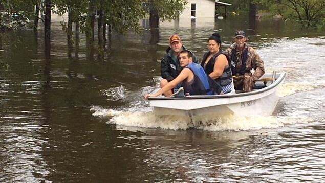 Des gens circulant à bord d'un canot à moteur.