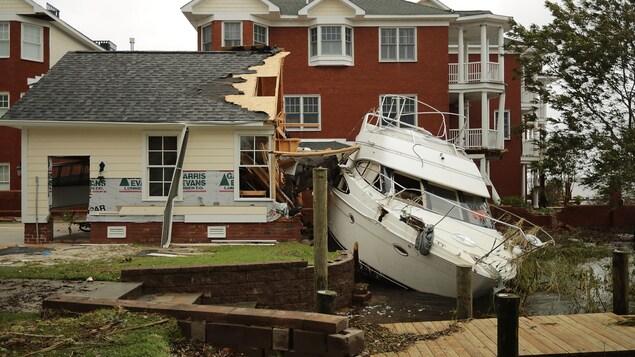 Un bateau blanc est à côté d'un garage en rénovation dont l'un des murs a été défoncé par le véhicule.