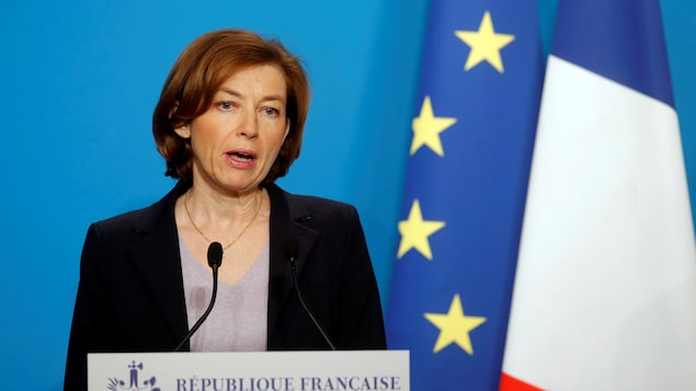 La ministre française de la Défense, Florence Parly, en train de faire une déclaration devant un lutrin sur lequel est écrit « République française ». Un drapeau de la France et de l'Union européenne sont accrochés derrière elle.