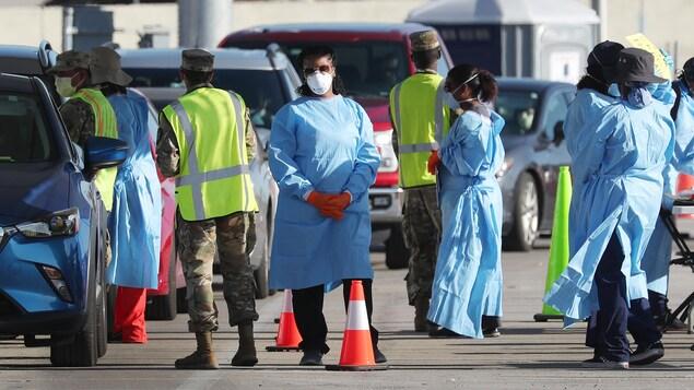 Du personnel en habit de protection médical se tient près d'une file de voitures.
