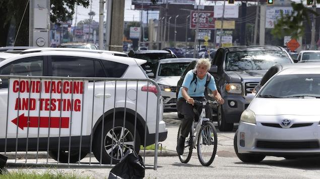 Un cycliste dans le trafic près d'une clinique de vaccination contre la COVID-19 à Orlando.